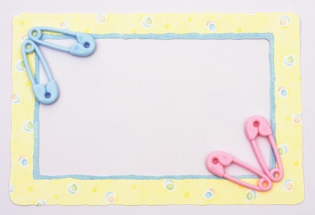 Pink and blue diaper pins sitting on a yellow alphabet background, baby border