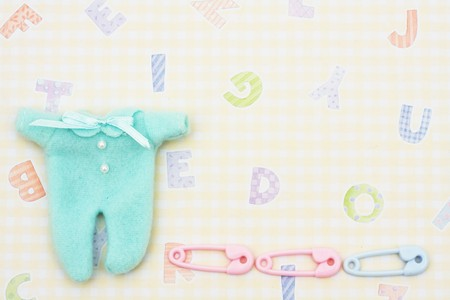 Baby sleeper with diaper pins sitting on a yellow alphabet background, baby sleeper photo