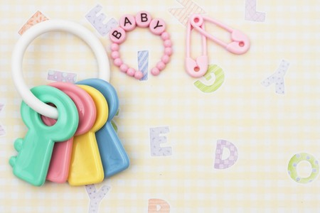 Key shaped baby rattle with pink bracelet and diaper pins sitting on a yellow alphabet background, baby rattle