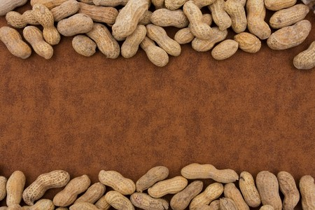 A pile of peanuts in the shell making border on a brown background, peanut border Stock Photo