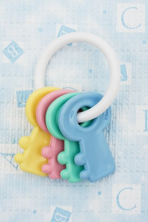 Key shaped baby rattle sitting on a blue alphabet background, baby rattle photo