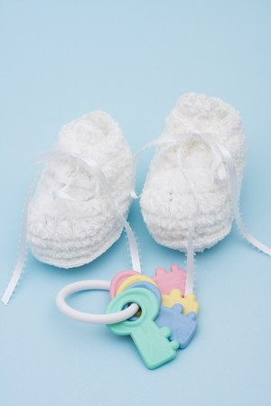 Baby booties and rattle sitting on a blue background, baby booties photo