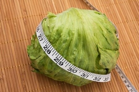 A head of lettuce with measuring tape sitting on a  wooden background, weight loss