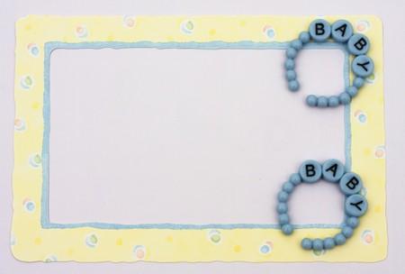 Blue baby bracelets sitting on a yellow alphabet background, baby border photo