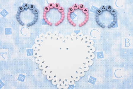 Blue and pink baby bracelets sitting with a white  heart on a blue alphabet background, baby bracelets photo