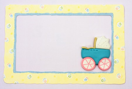 Pink and blue stroller sitting on a yellow alphabet background, baby border