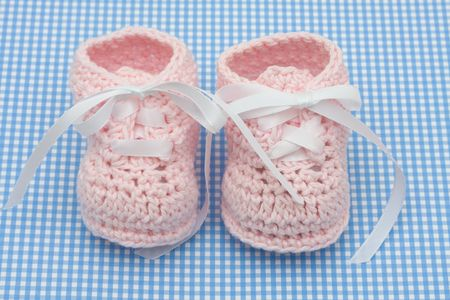 Pink baby booties on a blue background, baby booties photo