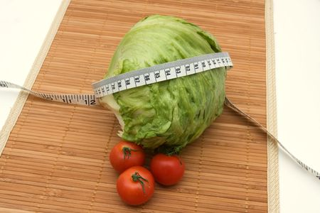 wooden metre: A head of lettuce and tomatoes with measuring tape sitting on a  wooden background, weight loss