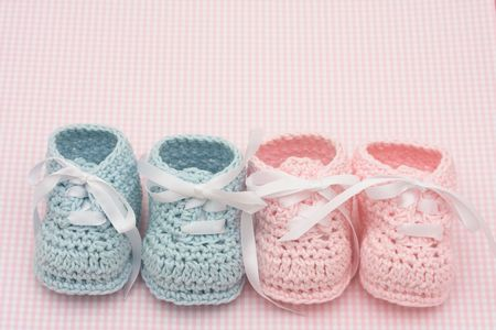 Blue and pink baby booties on a pink background, baby booties Reklamní fotografie