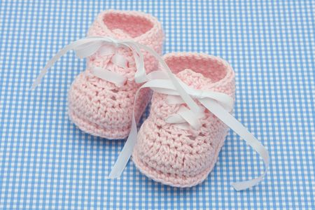 Pink baby booties on a blue background, baby booties Reklamní fotografie