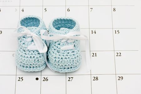 Blue baby booties on a calendar background, baby due date