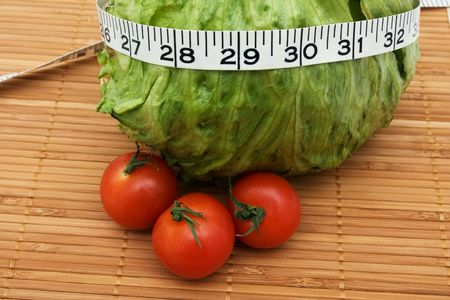 A head of lettuce and tomatoes with measuring tape sitting on a  wooden background, weight loss