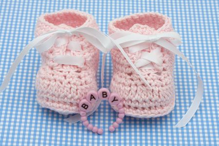 Pink chaussons bébé avec un bracelet sur un fond bleu, les chaussons pour bébés