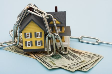 locked: A model house with a metal chain and cash on a blue background, house with chains