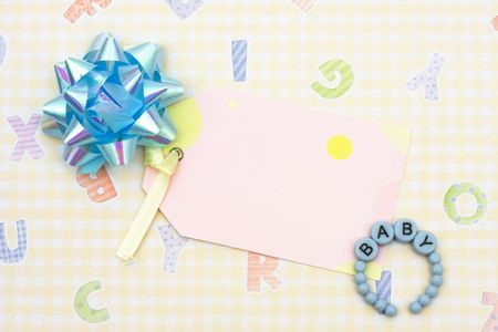 Blank tag with blue ribbon and baby bracelet sitting on a yellow alphabet background, blank tag photo