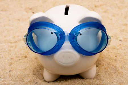 swimming goggles: A piggy bank wearing swimming goggles on a sand background, vacation savings