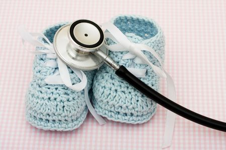 healthcare costs: A pair of blue baby booties and a stethoscope on a pink background, Healthcare Costs