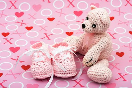 A pink handmade teddy bear and baby booties on a love background, I love you bear