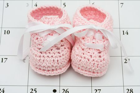 due date: Pink baby booties on a calendar background, baby due date