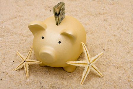 A piggy bank with starfish on a sand background, vacation savings Banque d'images
