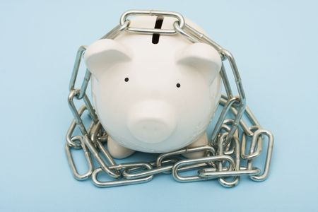 A piggy bank with a metal chain on a blue background, piggy bank with chains photo