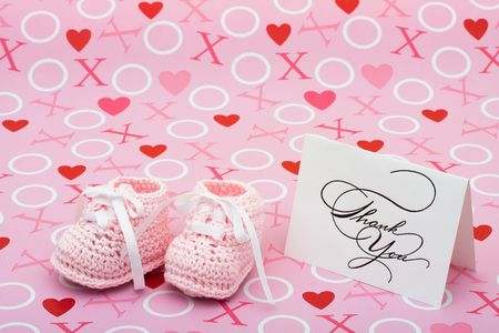 A white thank you card with baby booties on a pink love background, thank you note photo