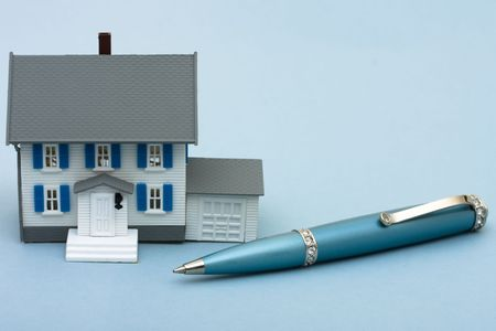 A blue pen with a model house sitting on a blue background, applying for a mortgage