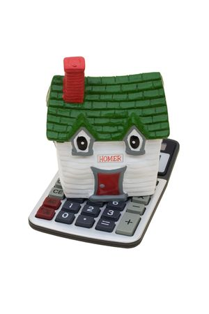 A model house sitting with a calculator on a white background, mortgage calculator photo