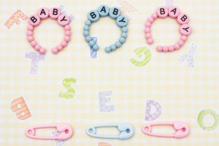 Pink baby bracelets with diaper pins sitting on a yellow alphabet background, baby bracelets photo