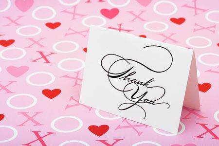 A white thank you card on a pink love background, love note photo