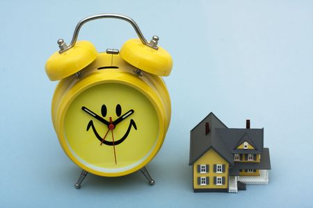 refinance: A model home with a clock sitting on a blue background, time to refinance your home