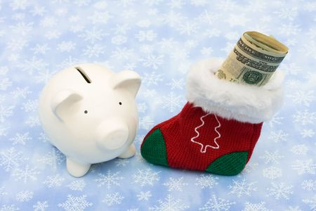 christmas sock: A piggy bank with a Christmas stocking sitting on a snowflake background, Christmas savings Stock Photo
