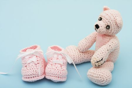 A pink handmade teddy bear and baby booties on a blue background, pink teddy bear photo