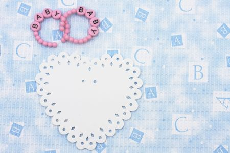 Pink baby bracelets sitting with a white  heart on a blue alphabet background, baby bracelets photo