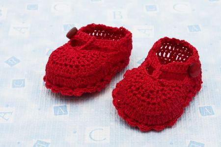 Red baby booties sitting on a blue alphabet background, baby rattle photo