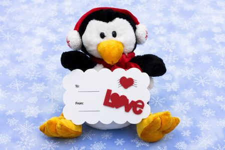 A penguin wearing a hat and scarf and holding an I love you postcard sitting on a snowflake background , merry Christmas photo
