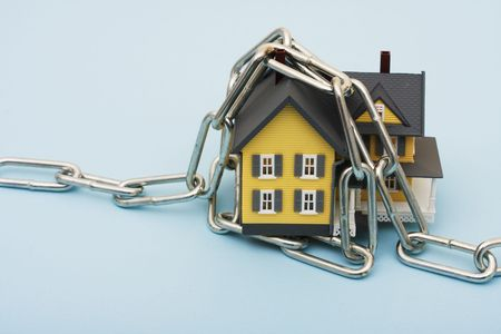locked: A model house with a metal chain on a blue background, house with chains