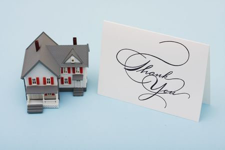 A model house with a thank you card sitting on a blue background, housing market photo