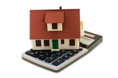 white interest rate: A model house sitting with a calculator on a white background, mortgage calculator