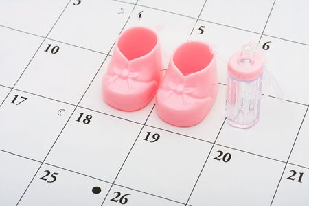 due date: Pink booties and bottle on a calendar background, due date