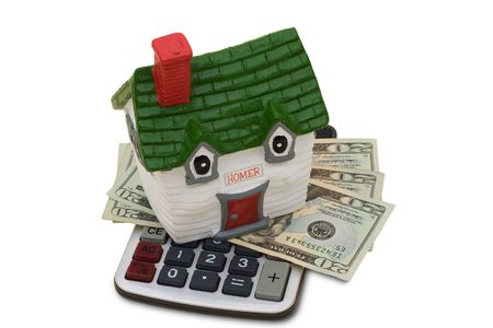 lend: A model house sitting with a calculator and twenty dollar bills on a white background, mortgage calculator