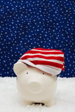 christmas savings: Piggy bank wearing Christmas stocking cap sitting on snow with star background, Christmas savings