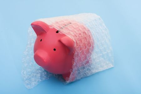A piggy bank with bubble wrap on a blue background, protecting your money photo