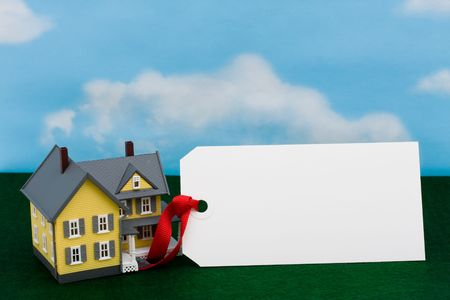 housing prices: A model house sitting with blank tag on a sky background, housing prices