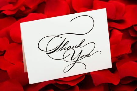 A white thank you card sitting on a red rose petal background, love cakes photo