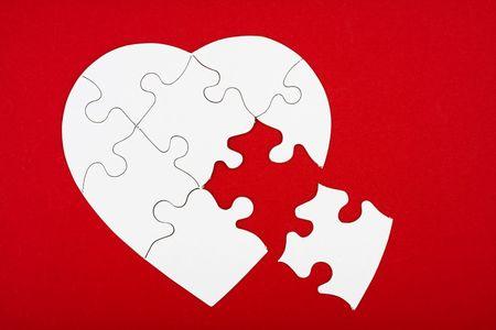puzzelen: Een witte hart vorm puzzel op een rode achtergrond, het hart vorm puzzel Stockfoto