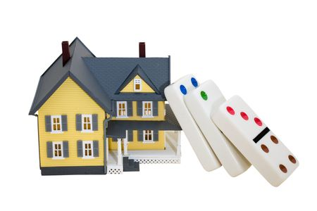 housing prices: A model house sitting with dominoes, falling housing prices