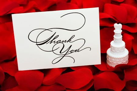 thanking: A white cakes with a heart on top and thank you card sitting on a red rose petal background, love cakes