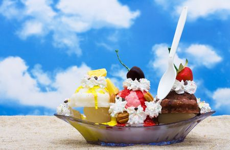 A banana split ice cream sitting on sand with a sky background, yummy