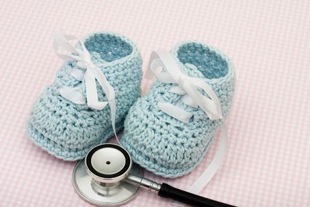 healthcare costs: A pair of blue booties and a stethoscope on a pink background, Healthcare Costs